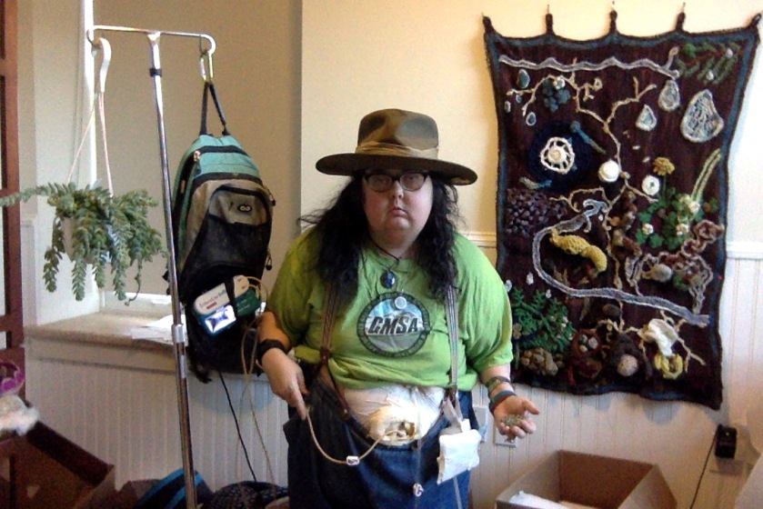 Mel wearing a hat, jeans, and a Green Mountain Self-Advocates t-shirt, with feeding tubes showing, standing next to an IV pole with a feeding bag on one side and a potted succulent on the other. There is an elaborate crocheted wall hanging showing different parts of the forest floor on a redwood forest. Including soil, water, slime molds, fungus, tree roots, plants, slugs, a snail, a newt, redwood cones, and random forest debris.