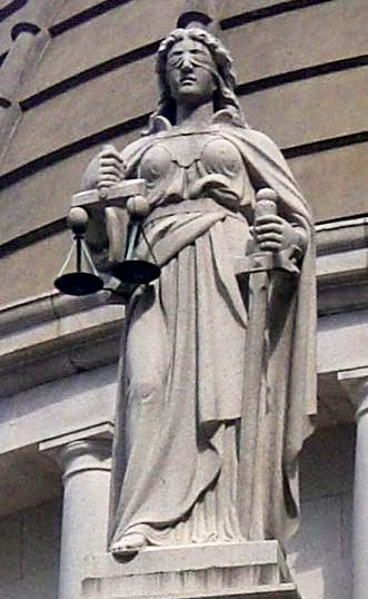 A statue of the blindfolded Lady Justice holding scales and a sword.