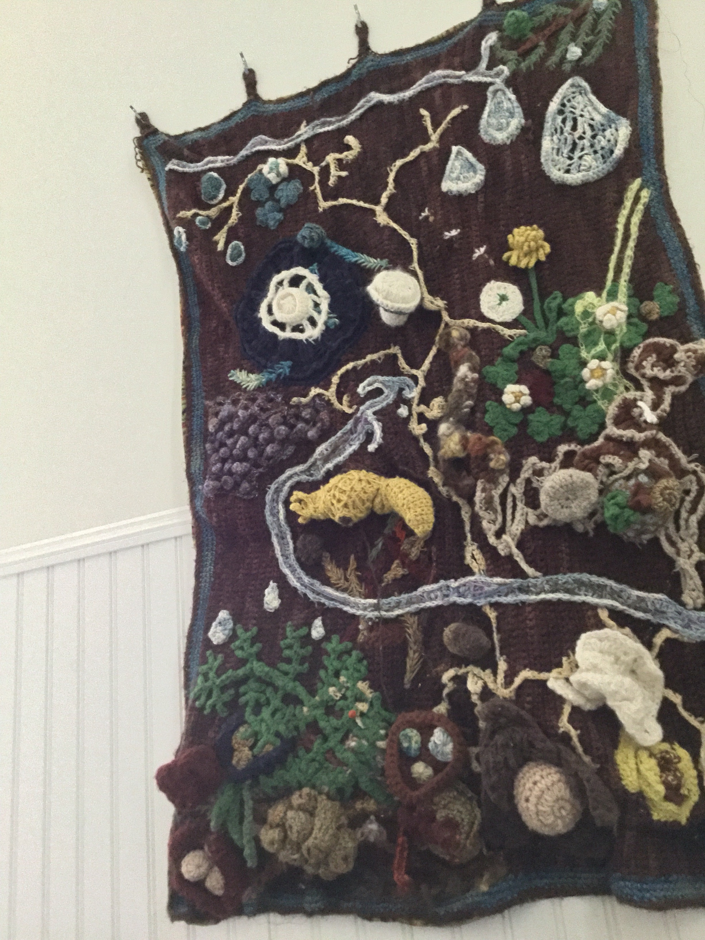 Elaborate crocheted wall hanging depicting the forest floor of Redwood Terrace.