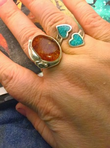 My hand with a large fiery-looking amber ring on it, as well as a turquoise ring with two hearts.