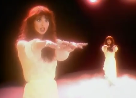 Kate Bush, arms outstretched in a white dress on a black background, shown from two views at once, performing in the music video to Wuthering Heights.