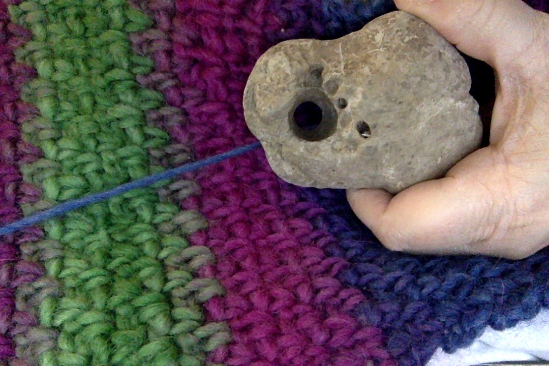 A rock with a natural hole in it, held over a colorful crochet pattern.