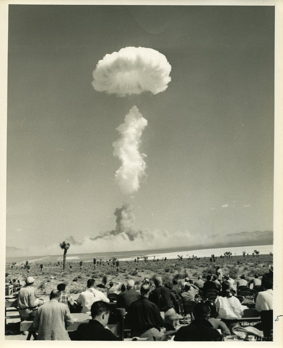 Black and white photo of mushroom cloud in the distance with a number of men sitting on the ground in the desert, watching. Cacti are visible in between the men and the mushrom cloud.