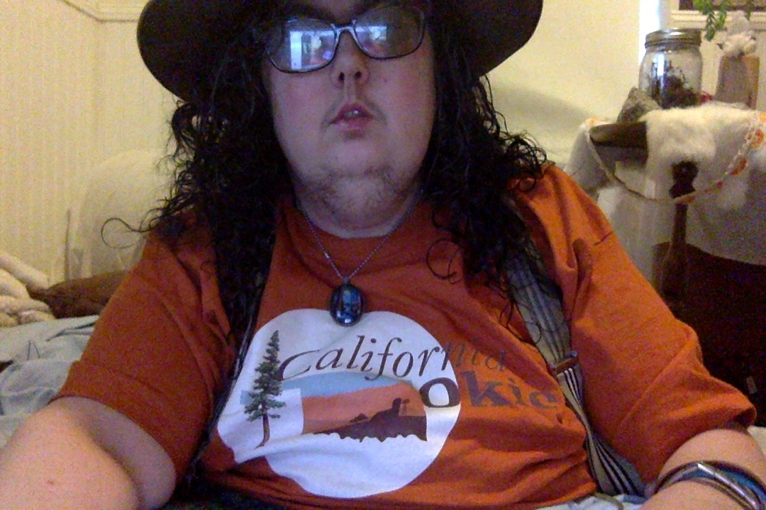 "Mel wearing an orange t-shirt that says ""California Okie"" with a picture of a redwood tree and a map of Oklahoma."