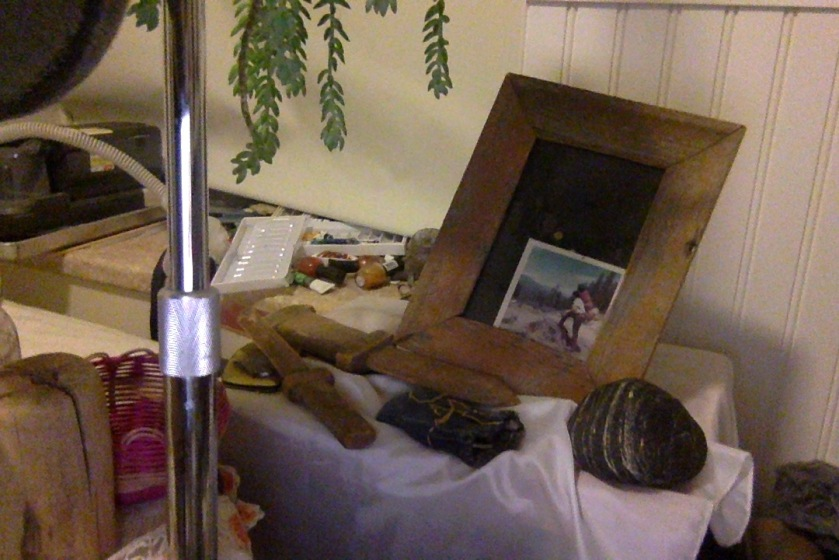 My father's memorial shrine, with the picture knocked off-kilter, only one rock out of dozens, and a few of his childhood belongings including a small denim treasure bag and a couple wooden toy swords. The slide rule is not visible, and the other slide rule is missing. Lots of things are missing or moved from where they should be.
