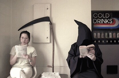 A woman sits next to a grim reaper in a laundromat, both reading books looking bored.