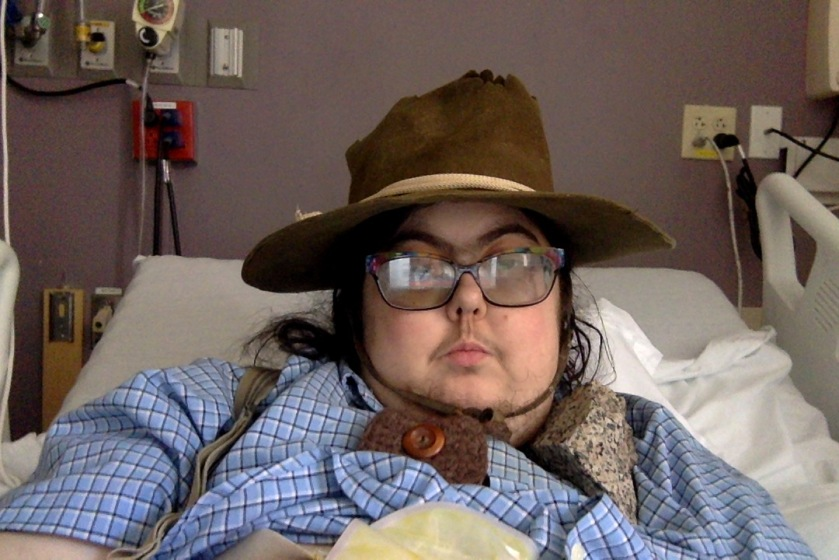 Mel wearing hir own clothes (button-down shirt, suspenders, hat) in the hospital the other day, with a piece of granite near hir shoulder.