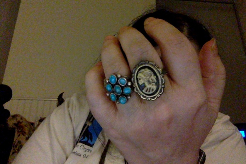 A big but elegant costume jewelry type ring showing a cameo death's head with an elaborate hairdo and a frilly border. Next to a handmade ring that's silver with a cluster of seven turquoises.