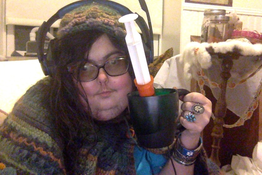 Mel with headphones on, smiling and holding up a green coffee mug of kombucha with a feeding syringe sticking out of it.